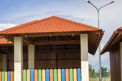 New modern alcove on kindergarten playground with bright orange tiling roof on blue sky background. royalty free stock photo