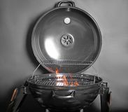 New modern barbecue grill with coals. On black background stock photography