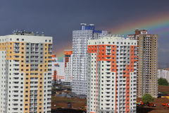 New modern block multistory house on dark sky background in four colors: red, orange, grey and white. Bad weather and rainbow. Bui Royalty Free Stock Image