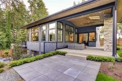 New modern home features a backyard with patio. New modern home features a backyard with covered patio accented with stone fireplace, vaulted ceiling with Royalty Free Stock Photos