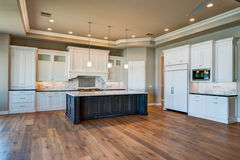 New Modern Home Mansion Kitchen. Brand new modern model home kitchen with center island and wood floors Royalty Free Stock Image