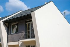 New modern house with plastic windows, metal roof, ventilation, chimney and rain gutter. Royalty Free Stock Image