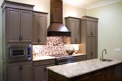 New Modern Kitchen. New modern luxury kitchen cabinets, with gas stove and granite countertops and high ceiling Royalty Free Stock Photography