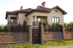 New modern luxurious expensive residential two story cottage house with shingle roof, big windows and balconies behind stone fence. With iron forged gate. Real stock photos