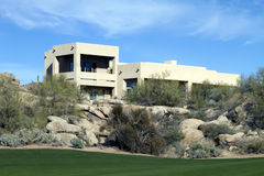 New modern luxury desert golf course home. New modern luxury desert homes nestled in the mountains alongside a golf course Royalty Free Stock Photos
