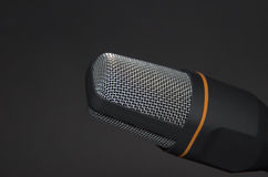 New modern microphone recording device on black background. Stock Image