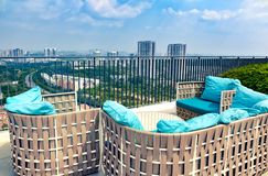 New modern terrace, balcony on roof of high rise building with beautiful view of cityscape. Picturesque patio with wicker soft sofa for rest. Malaysia stock photo