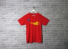 New Mon State Party flag on shirt and hanging on the wall with brick pattern wallpaper. Flag of the golden drake flying on red to star royalty free stock photo