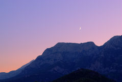 New moon over a mountains.  Stock Images