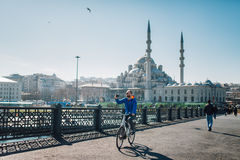 New Mosque (Yeni Cami). A cyclist is making a photo selfie from the Galata Bridge and with the New Mosque (Yeni Cami) in the background, Istanbul, Turkey royalty free stock photography