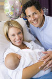 New mother with baby and husband in hospital Royalty Free Stock Photo