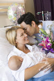 New mother with baby and husband in hospital Royalty Free Stock Photos