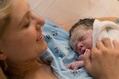 New mother happily holding her newborn child moments after labor Royalty Free Stock Photos