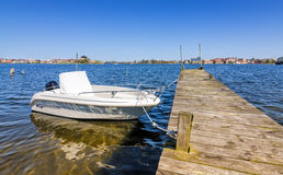 New motorboat moored to wooden bridge Stock Images