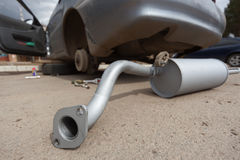 The new muffler against the dirty car Royalty Free Stock Images