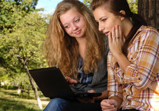 New netbook. Two teenage girls having fun with laptop outdoors Royalty Free Stock Image