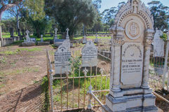 New Norcia Cemetery: Fenced Headstones. NEW NORCIA,WA,AUSTRALIA-JULY 15,2016: Ornate old gravestones in garden fencing at the New Norcia Cemetery with treed Stock Image