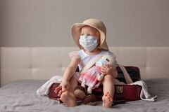 Free New Normality Travel, Happy Little Girl Sun Hat And Medical Mask Sits Burgundy Open Suitcase, Hugging Toy Knitted Rabbit Royalty Free Stock Image - 217248106