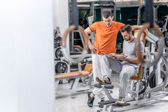 New occupations. Two young smiling athlete sit among trainers in. The fitness gym and watching a sports magazine. Beautiful young people are smiling and happy stock image
