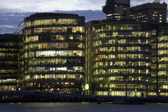 Offices in London. New office buildings with lighted windows at dusk along the Thames in London, UK Royalty Free Stock Photos