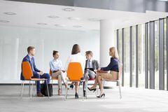Business colleagues planning strategy while sitting on chairs during meeting royalty free stock photo