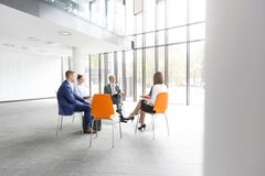 Business colleagues planning strategy while sitting on chairs during meeting royalty free stock images