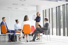 Businesswoman planning strategy with colleagues during meeting at office royalty free stock images