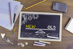 New and Old Balance. Chalkboard on wooden office desk Royalty Free Stock Photo