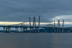 Tappan Zee Bridge - New York. New and Old Tappan Zee Bridges coexisting across Hudson River with a dramatic sunset royalty free stock image