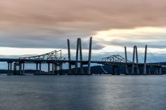 Tappan Zee Bridge - New York. New and Old Tappan Zee Bridges coexisting across Hudson River with a dramatic sunset royalty free stock photo
