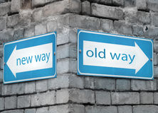 New and old way directions. Two blue light directions arrow at the angle on a grey old brick wall with the text new and old way Royalty Free Stock Photo