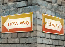 New and old way. Two direction arrow at the angle of an old brick wall with the text new and old way Royalty Free Stock Photos