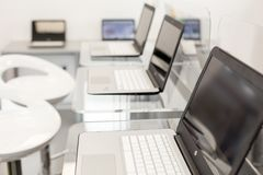 New, open laptops, on a glass desktop; modern white chairs in background Royalty Free Stock Photo