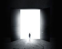 New opportunity. Rear view of businessman standing in light of opened door Royalty Free Stock Photography
