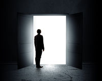 New opportunity. Rear view of businessman standing in light of opened door Stock Images