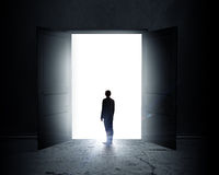 New opportunity. Rear view of businessman standing in light of opened door Stock Image
