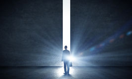 New opportunity. Rear view of businessman standing in light of way in wall Royalty Free Stock Photography