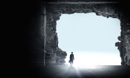 New opportunity. Rear view of businessman standing in light of way in wall Royalty Free Stock Photo