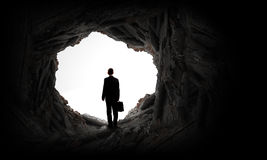 New opportunity. Rear view of businessman standing in light of way in wall Stock Photo