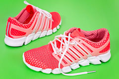 New orange and white running shoe, sneaker or trainer on green b Stock Image
