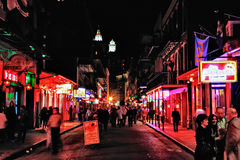 New Orleans Bourbon Street at Night. A bright, colorful nighttime shot from the middle of Bourbon Street looking at the bars, gentlemen's clubs and music halls