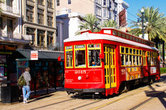 New Orleans Canal Street Street Car Stop. A street car stop along with one of the many bright red and yellow easily accessible street cars running on Canal Stock Images