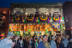 New Orleans, LA/USA - circa March 2011: People throwing beads and watching celebration from balconies during Mardi Gras in New Orl royalty free stock images