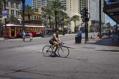 Street scene at Canal Street with a man on a bicycle in the downtown of the city of New Orleans, Louisiana. New Orleans, Louisiana - June 18, 2014: Street scene royalty free stock images
