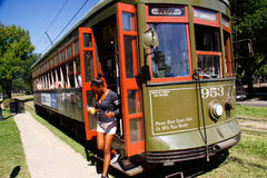 New Orleans Person Exiting Street Car. A female passenger exits the front door of one of the historic green St. Charles Avenue street cars running along the edge Stock Photo