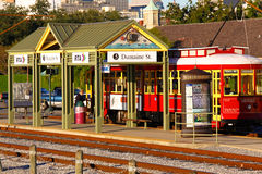 New Orleans Riverfront Street Car Stop. A street car stop along with one of the many bright red and yellow easily accessible street cars running on the Royalty Free Stock Photos