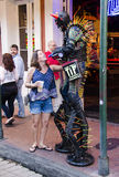 New Orleans, USA - July 8, 2015: A street performer dressed as a monster being is photographed for tips on Bourbon Street. Royalty Free Stock Images