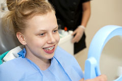 New orthodontic brace. Happy young looking at her new orthodontic brace in the mirror Royalty Free Stock Image