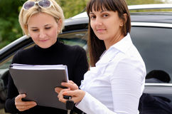 New owner purchasing a car. New attractive blond female owner purchasing a car from a smiling saleslady as they stand together alongside the vehicle signing the Stock Image
