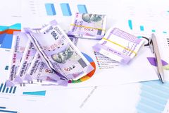New pack of Indian 100 Rupee notes with chart paper and pen. Isolated on wooden background stock images